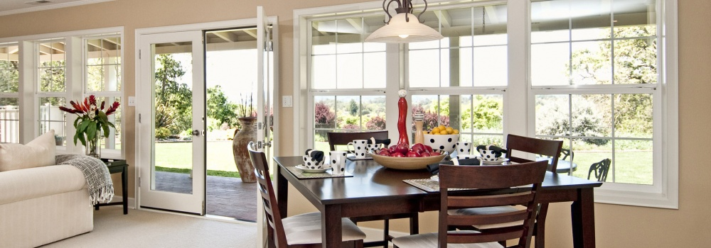 Dinning area with large window views, nice wooden table with table settings, french doors